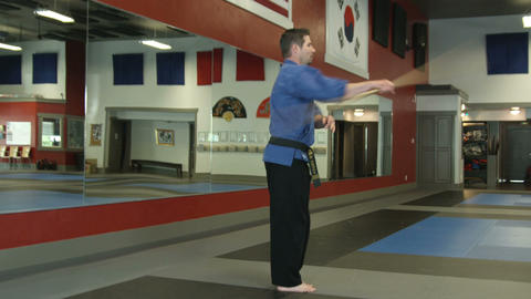 Man in a karate studio practing bow staff weapon moves Footage