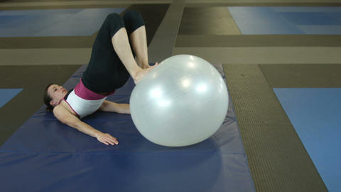 Female doing leg workout with workout ball Footage