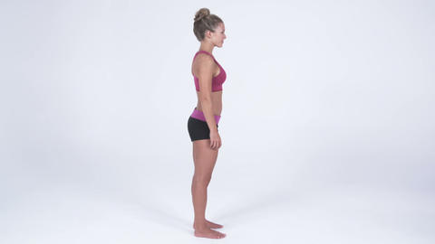 Right side view of a young woman in yoga attire, putting hands on hips Footage