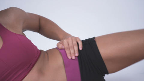 Close up panning shot of young woman laying on her side doing leg exercises Footage