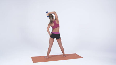 Back shot of a young female standing on a yoga mat lifting a weigt over her head Footage