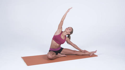 Young woman sits on a yoga mat and does arm stretches Footage