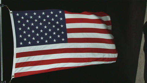 American flag waving in the wind with black background Footage