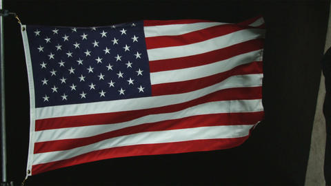 The American flag waving in the wind with black background Footage