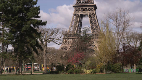 Base of the Eiffel Tower with trees and traffic Live Action
