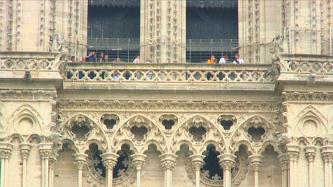 People on the balcony of the Notre Dame Cathedral towers in Paris Live Action