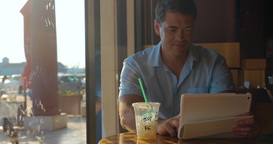 Man using tablet computer in cafe Footage