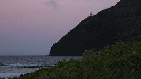 Lighthouse on a rocky cliff above the ocean at sunset in Hawaii Live Action