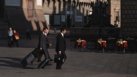 Business men walking with luggage through a plaza in Bologna Italy Live Action