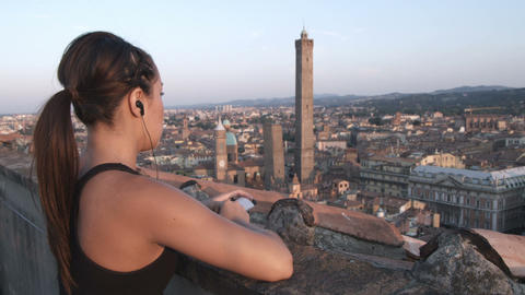 Woman jogger listening to music as she overlooks an Italian city Footage