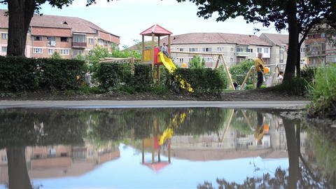 Playground for children is seen reflected in a puddle on the outskirts of 01 Footage