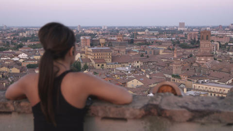 A woman jogger listens to music as she overlooks an Italian cityscape Footage