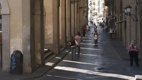 People and scooters passing by an old archway in Italy Footage