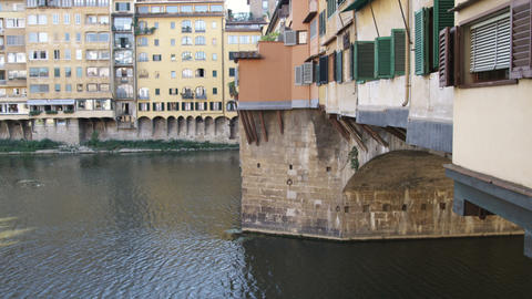 Tilt up from water to bridge with houses in Italy Footage