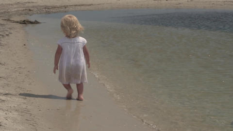 Beautiful little girl runs along the seashore. Little girl in a white dress on Live Action