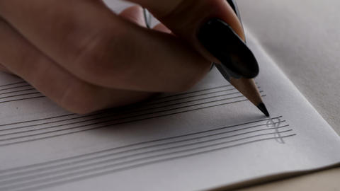 Musician or composer hand writes a song or a musical work ビデオ