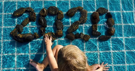 Kid in swimming pool and make pebble rock arranged Footage