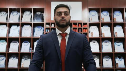 Businessman choosing classical suit in the suit shop Live Action