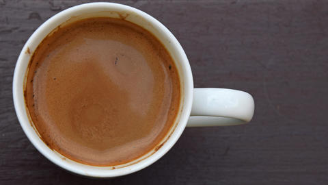 Full cup of coffee with milk on table GIF