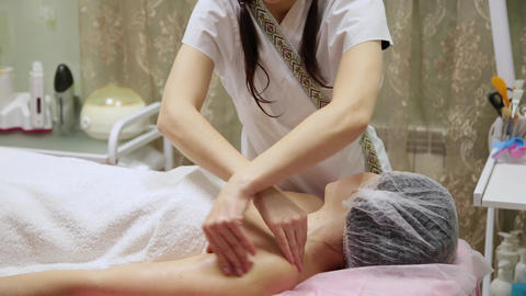 Attractive female at spa health club getting a facial massage. Beautician doing Live Action