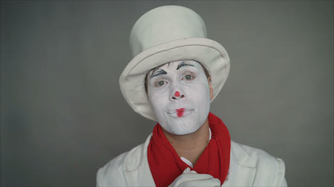 Mime looks sad holding hands before his chest. Sad mime in a white hat and Live Action