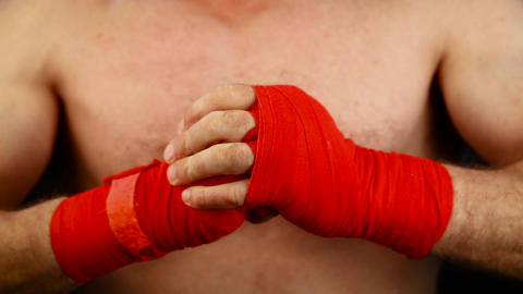 Close up man boxer tightens wrists with red wrap GIF