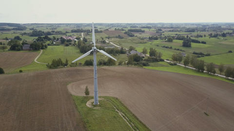 Aerial view of small single wind turbine rotating fast. Summer countryside with Footage