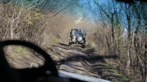 Driving off-road car throgh a forest. Driving old-fashioned off-road jeeps Live Action