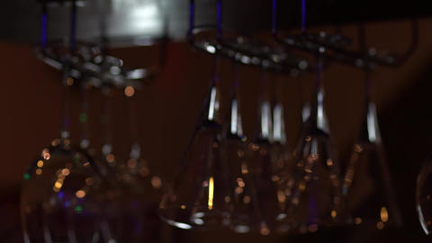 Various glass goblets hang from the dish rack above the counter Footage