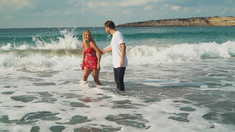 Happy couple going to swim in waves. Leisure of cute young family Footage