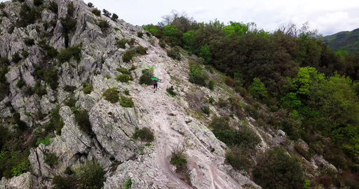 Aerial shot of a mountain biker lifting his bike on top of the mountain Live Action