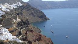 Greece Aegean Sea Cyclades Santorini steep coast of Fira & sailing boats below ビデオ