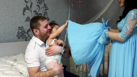 Parents happily dress up their little daughter in a dress Footage