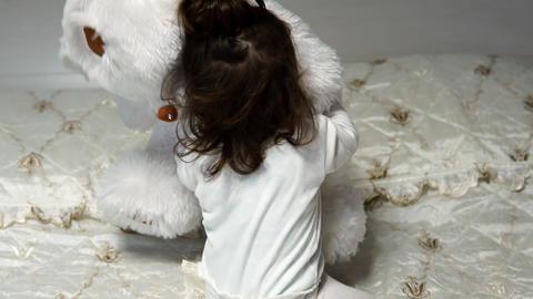 A little girl hugs her favorite soft bear toy Footage