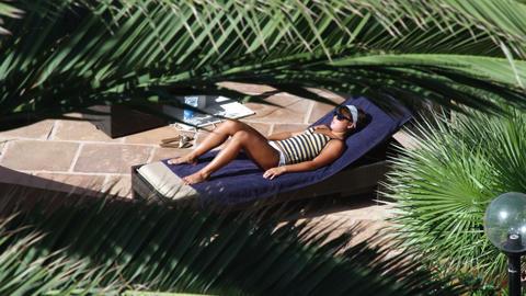 Sunbathing woman at a resort pool side Footage