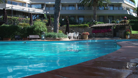 Woman diving in a swimming pool at resort. Surfaces near and smiles at the camer Footage