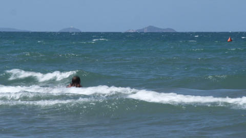 Woman riding the waves on a boogie board, in Italy Footage