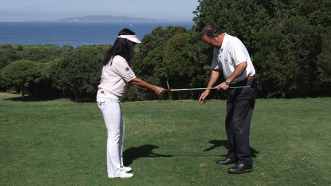 Golf trainer showing woman propper stance Footage