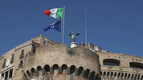 Two flags on a flag pole atop a stone structure in Rome Italy Footage
