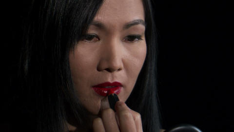 Woman putting on lipstick on a black background, Live Action