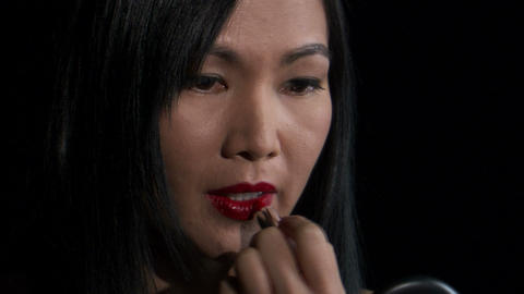 Woman putting on lipstick on a black background Live Action