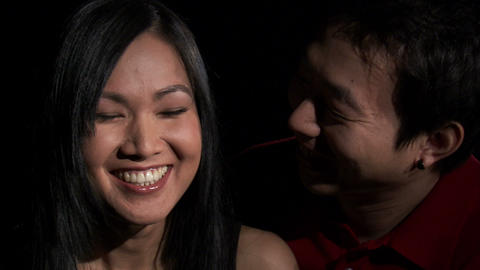 Close shot of a man kissing a woman's cheek on a black background Live Action
