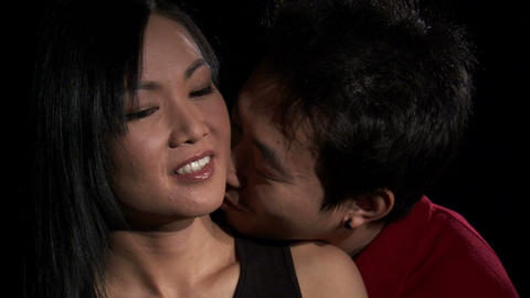 Man kissing a woman's neck on a black background Live Action