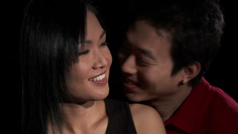 Man kissing a woman's neck on a black background, Live Action