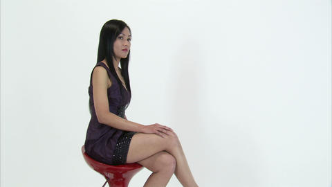 Woman turning on a red chair to look at the camera Live Action