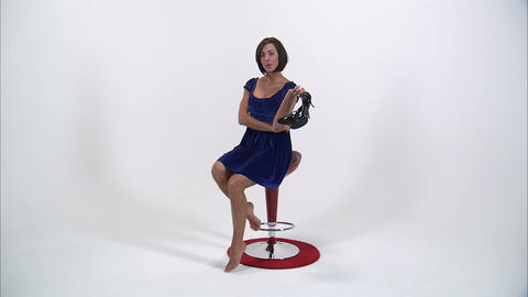 Woman sitting on a chair holding shoes and looking agitated Footage