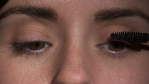 Close up on a woman's eyes as she applies mascara Footage