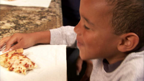 Close up of a boy eating pizza Footage