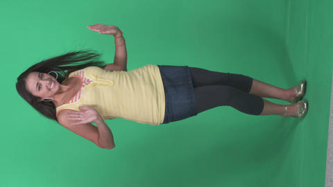 Young dark haired girl dances against a green screen Footage