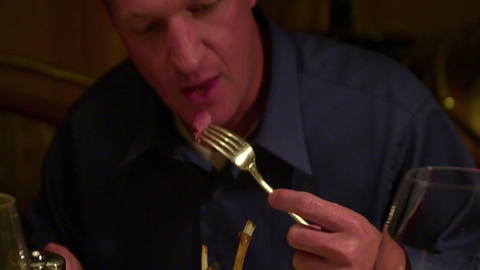 Close up of a man eating a bite of steak Footage
